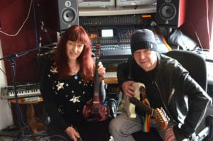kirsty mckinna and iain mckinna from harmonic overdrive, holding their instruments - violin and guitar